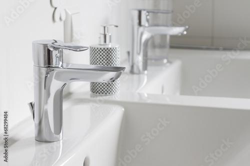 Leinwanddruck Bild Wasserhahn mit Seifenspender auf weißem Keramikwaschbecken