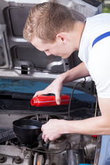 Mechanic changing car oil