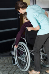 Nurse helping a disabled woman to enter the house