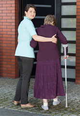 Woman helping elderly lady on crutches to enter house