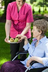 Nurse gives an older woman pears