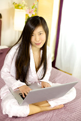 Cute asian woman sitting in bed with computer smiling