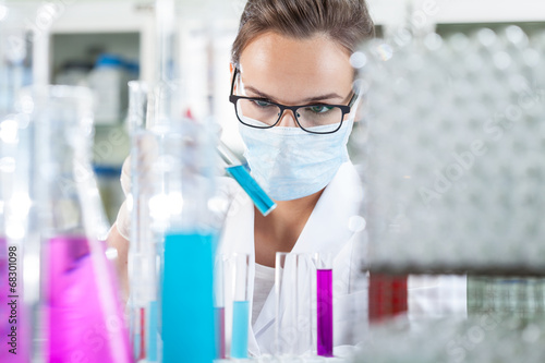 Woman analyzing liquid in test tube - 68301098