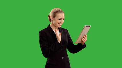 Young blond businesswoman speak for tablet on green screen.