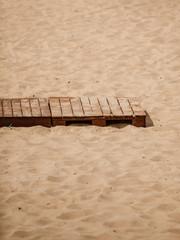 Summer resort. Wooden sidewalk on a sandy beach.