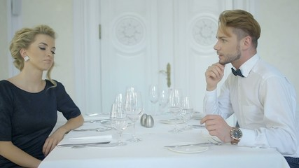 Young attractive couple talking at the luxury restaurant