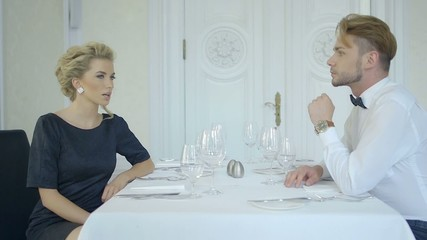 Footage of a dating couple talking at luxury restaurant