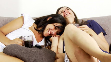 Two girlfriends having fun watching tv at home