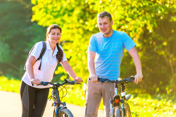 young couple on the weekend to ride a bike in the park