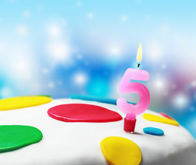 Burning candle with the number five on a birthday cake