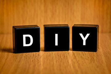 DIY or Do it yourself word on black block
