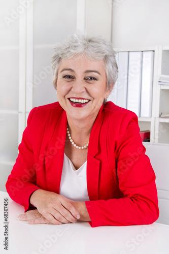 Portrait: Senior Chefin in Rot sitzend und lachend im Büro