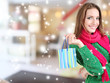 Beautiful young woman with gift bag in shop