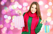 Beautiful young woman with gift bags on bright background