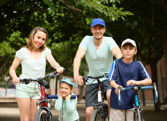 happy family of four with bicycles and scooter