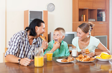 family having breakfast  with croissants and juice