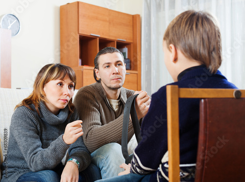 Parents with belt berating  son