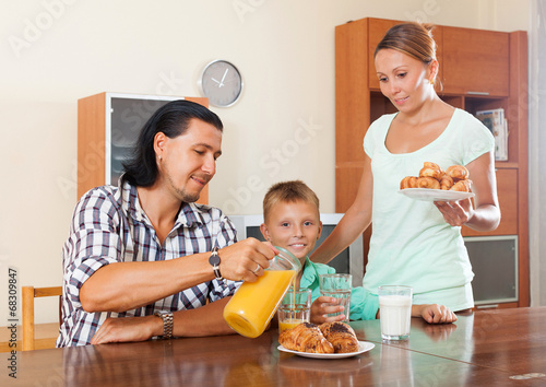 couple with teenager son having breakfast in home