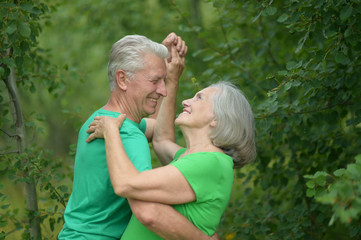 Senior couple dancing in a  forest