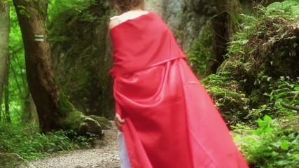 Mysterious red riding hood walking in forest