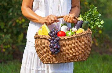 Woman holding basket full of fruits and vegetables