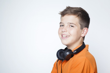 Smiling boy standing with headphones on the neck against grey ba