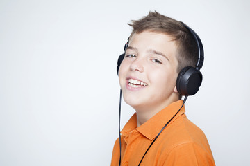 Smiling boy with headphones listening music against grey backgro