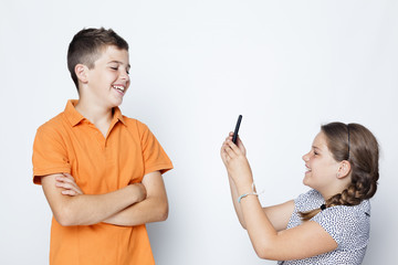 A boy and a girl taking pictures with smartphone against gray ba