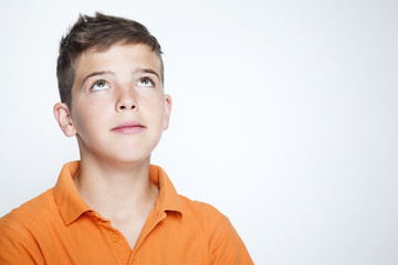 Closeup of a teenager boy looking up against gray background