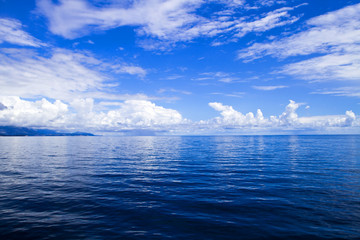 White clouds blue sky above the sea