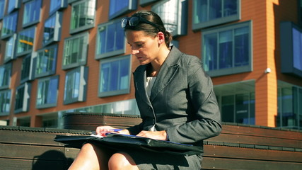 Businesswoman checking report and sitting in modern place