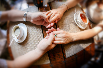 Hands of the guy and hand of the girl at a table