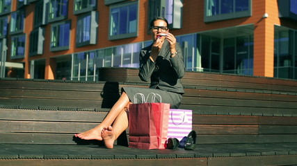 Businesswoman sitting and using red lipstick