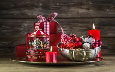 Weihnachten: Dekoration in Rot mit Geschenk und Kerze rustikal