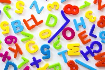 Letras y números de distintos colores sobre superficie blanca
