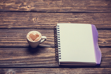 Cup of coffee with shape heart and notebook on wooden table.