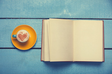 Cup of coffee with book on blue wooden table.