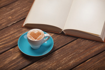 Cup of coffee with heart shape and book on wooden table.