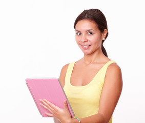 Cute latin female working on her pink tablet pc