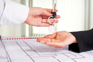 Architect hand presenting house key to a client.