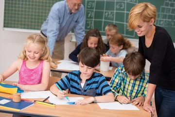 zwei lehrer betreuen eine grundschulklasse
