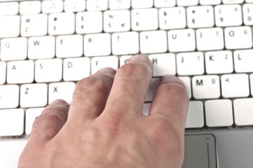 man's hand typing on laptop