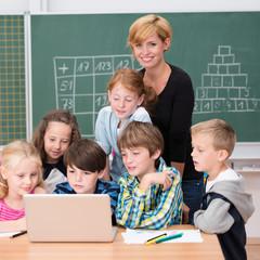 lächelnde lehrerin mit schulkindern am laptop