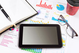 Business detail of a tablet lying on top of business charts