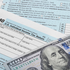 US Tax Form 1040 with 100 dollars banknote - 1 to 1 ratio