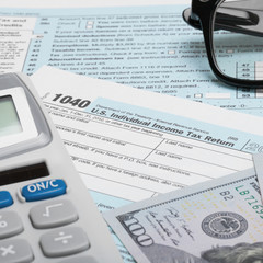 US Tax Form 1040 with calculator, dollars and glasses - 1 to 1
