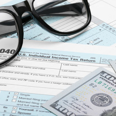 US Tax Form 1040 with dollars and glasses - 1 to 1 ratio