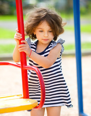 Young girl is playing in playground