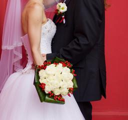 Happy groom hugs his bride with flowers
