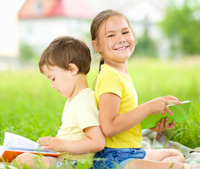 Little girl and boy are reading books outdoors